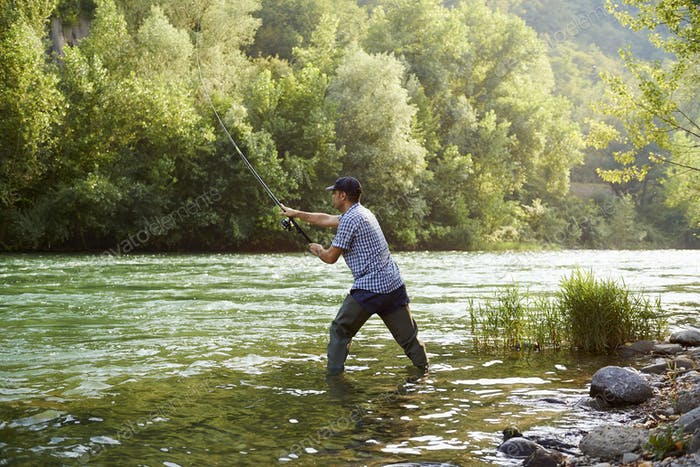 Fisherman Standing Near River And Holding Fishing Rod