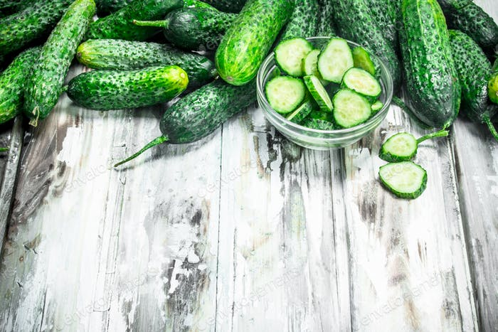 Cucumbers and cucumber slices in a glass bowl.