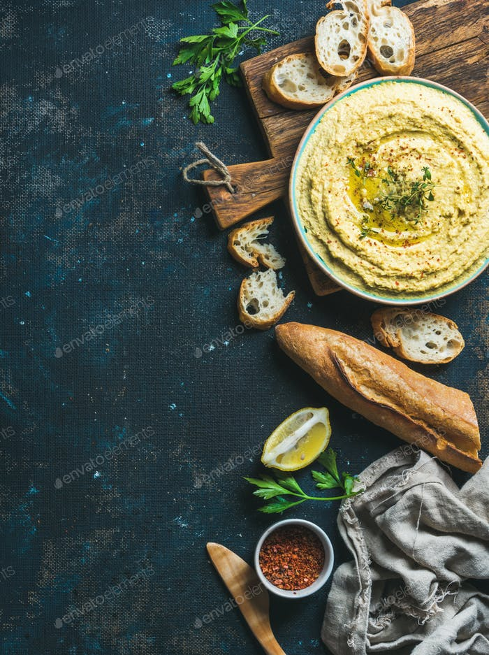 Homemade hummus dip with fresh baguette, lemon, herbs and spices