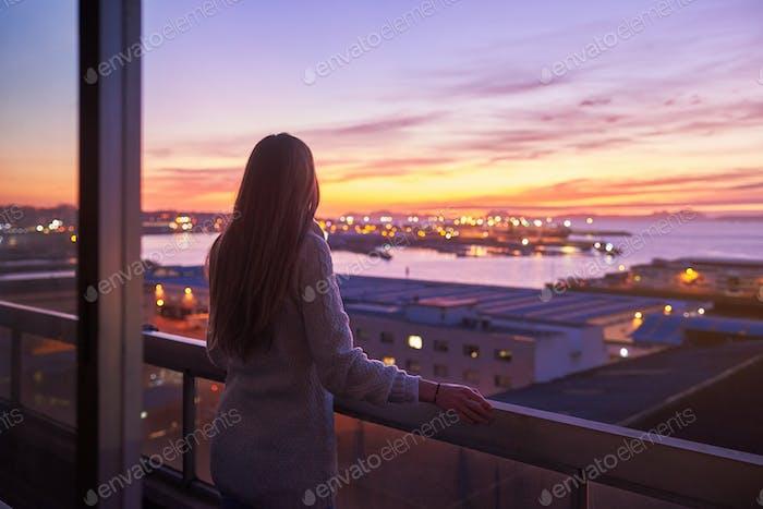 Mujer joven contemplando el mar desde un balcón