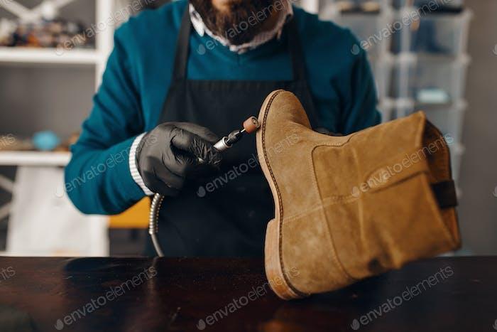 Schuhmacher schärft die Schuhsohle, Schuhreparatur