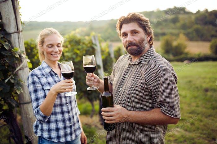 Wine tourists tasting wine in vineyard