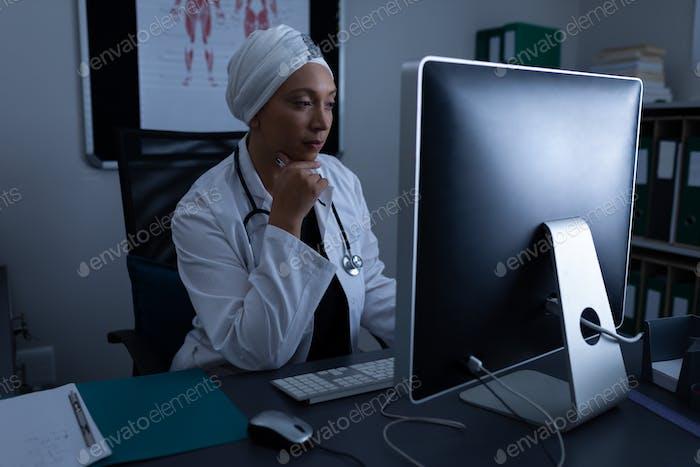Vorderansicht der nachdenklich gereiften gemischten Rasse Ärztin Arbeit am Computer in Klinik im Krankenhaus
