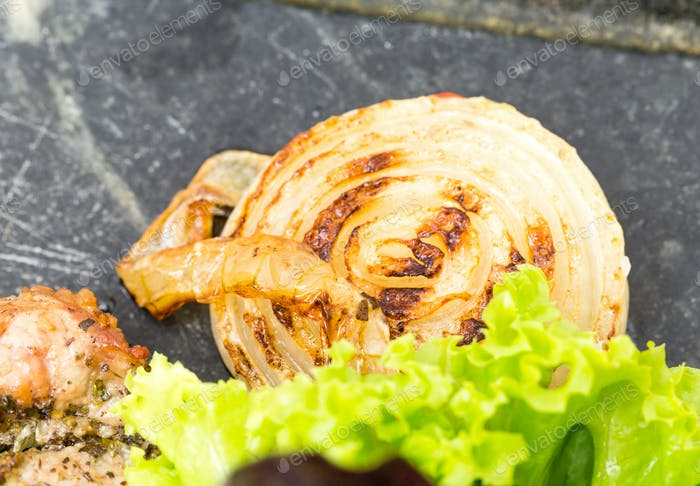 Grilled onion with lettuce on metal pan.