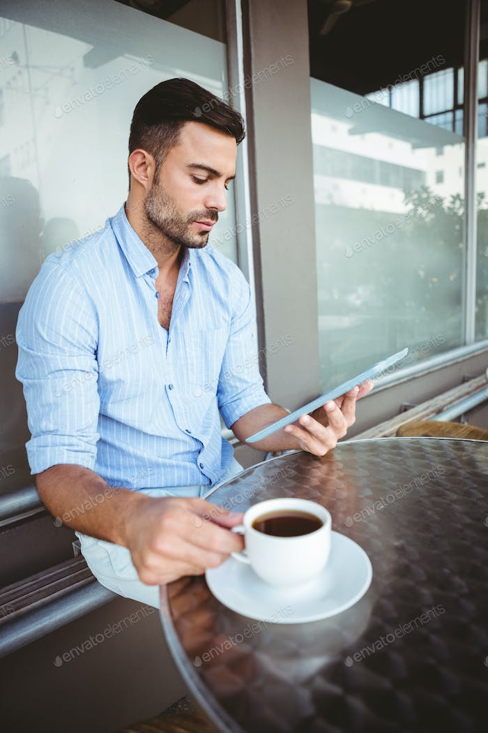 Attentive businessman using a tablet while holding coffee cup outside the cafe