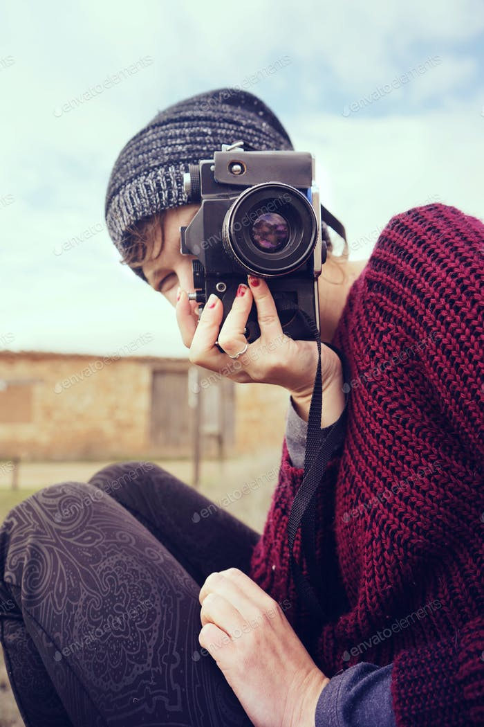Moody portrait of a young photographer with her camera