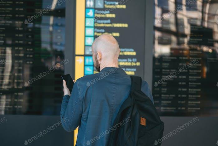 Schöner kahlbärtiger Mann im Anzug mit Rucksack liest Informationen am Flughafen