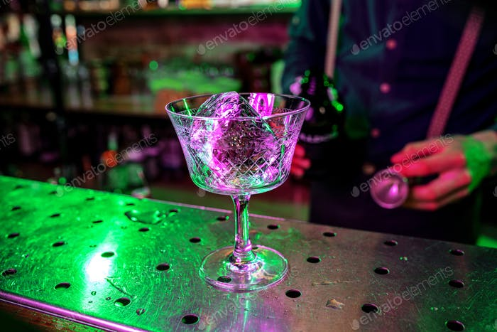 Close up of barman finishes preparation of alcoholic cocktail, pouring drink with shot in