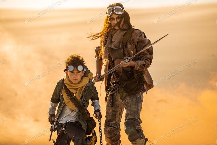 Post apokalyptische Frau und Junge im Freien in einem Ödland