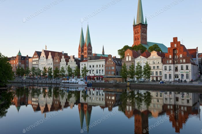 Church spires and gables of traditional houses reflected in the calm waters of a river.
