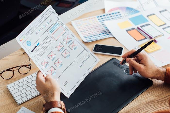 Vista recortada del diseñador usando la tableta Gráficos mientras planifica el diseño de la experiencia del usuario del sitio web en