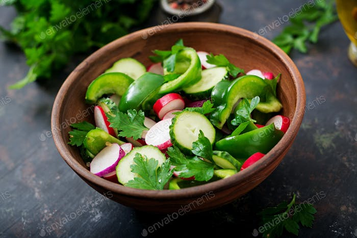 Fresh salad of cucumbers, radishes, green peppers and parsley.