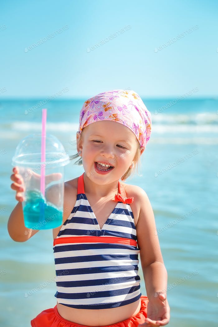 little girl in swimsuit drink cocktail on the beach.