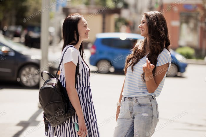Two youthful pretty slim girls,wearing casual outfit,stand at the street and chat
