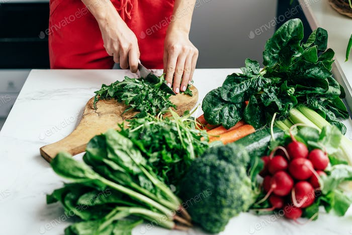 Female hands cut greens on a blackboard on a table. Cooking healthy food. Healthy lifestyle.