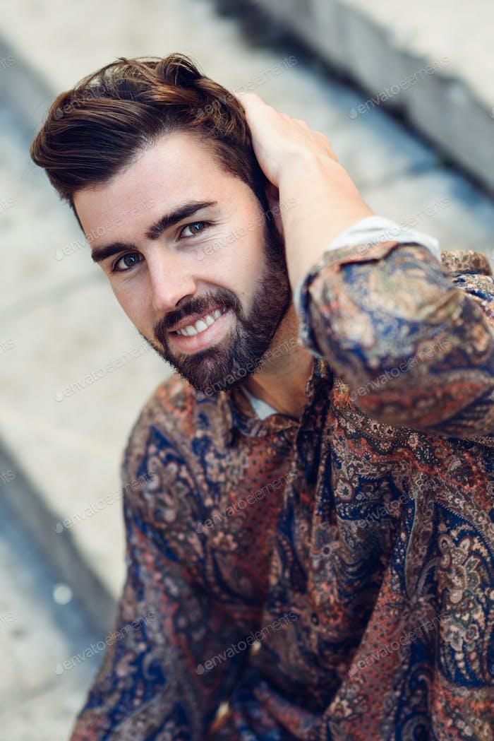 Young bearded man, model of fashion, wearing shirt in urban back