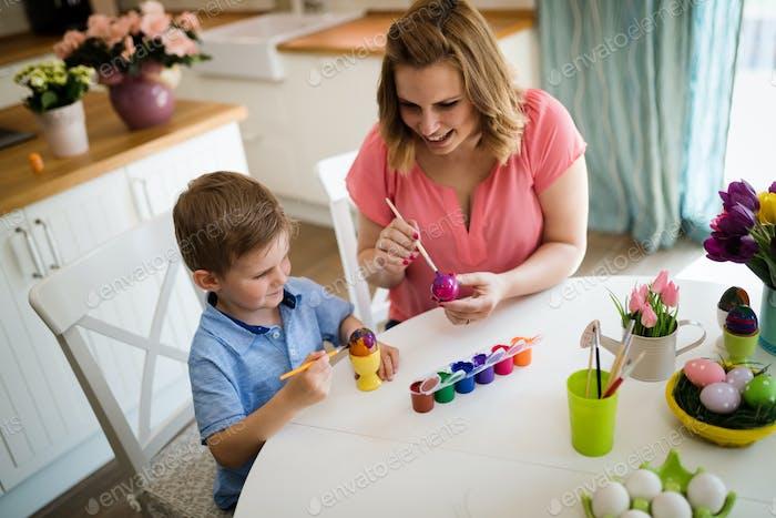 Glückliche junge Mutter und Sohn malen Ostereier
