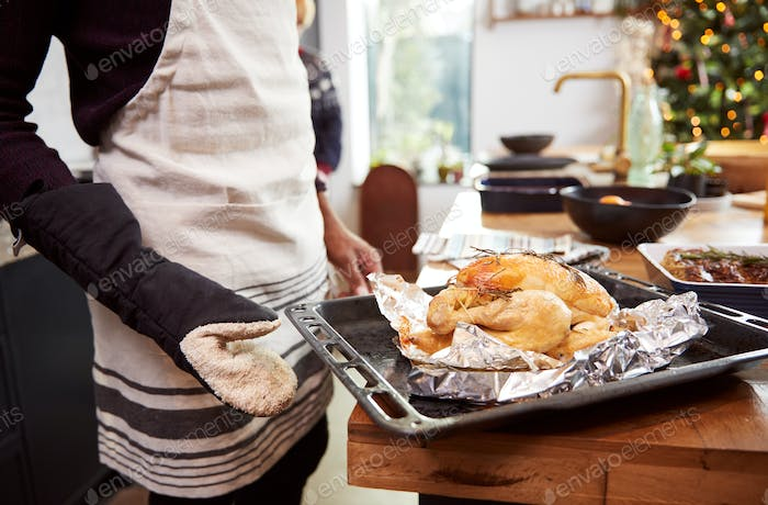 Close Up Of Man Taking Roast Chicken Out Of Oven For Christmas Dinner
