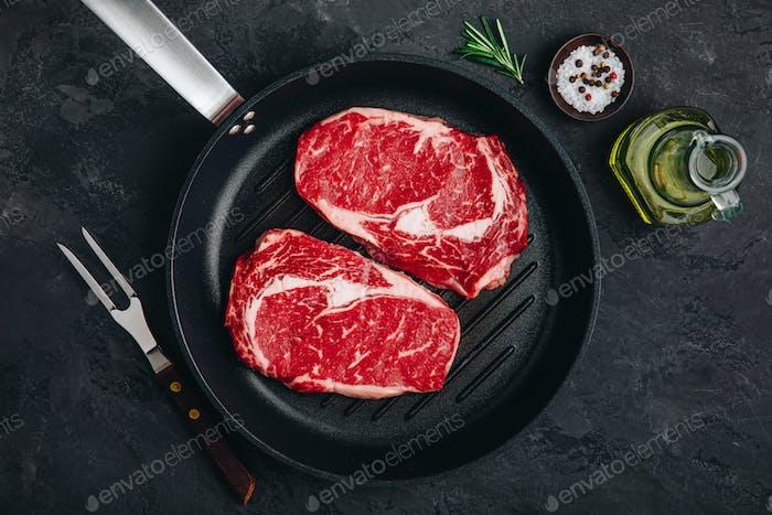 Ribeye Steak, rohes frisches Rindfleisch mit Salz und Rosmarin in Grillpfanne