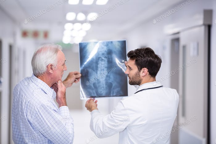 Doctor discussing x-ray with patient in corridor