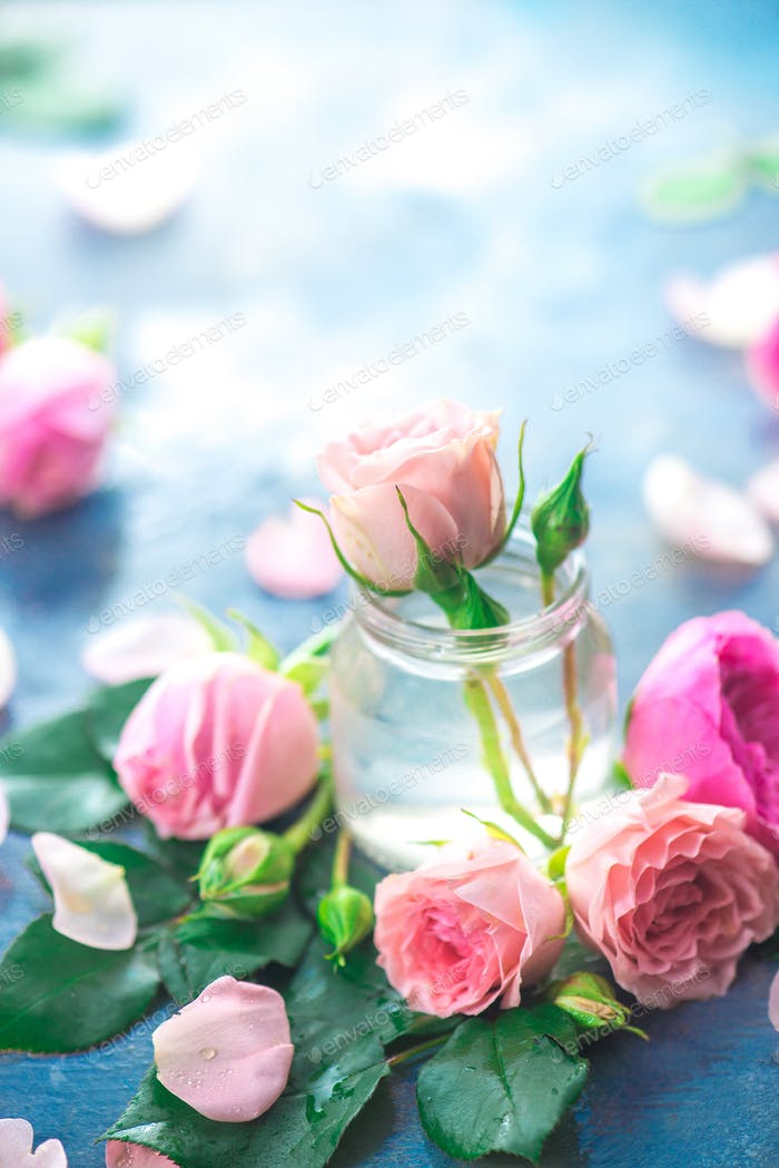Pink roses in tiny glass bottles on a neutral gray background with copy space. A feminine concept