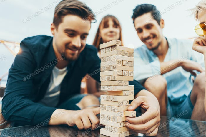 The company of young people playing jenga