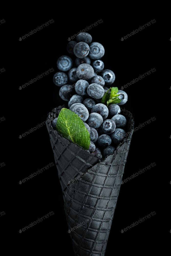 Black wafer cone with frozen blueberry fruits. Ice cream