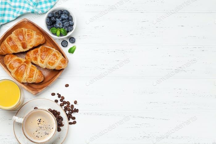 Coffee, juice and croissants breakfast