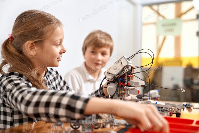 Boy and girl creating robot using building kit