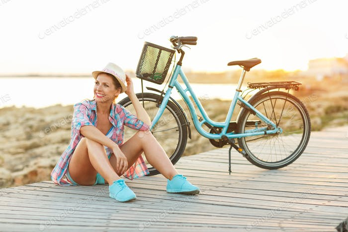 Carefree pretty woman with bicycle sitting on a wooden path at t