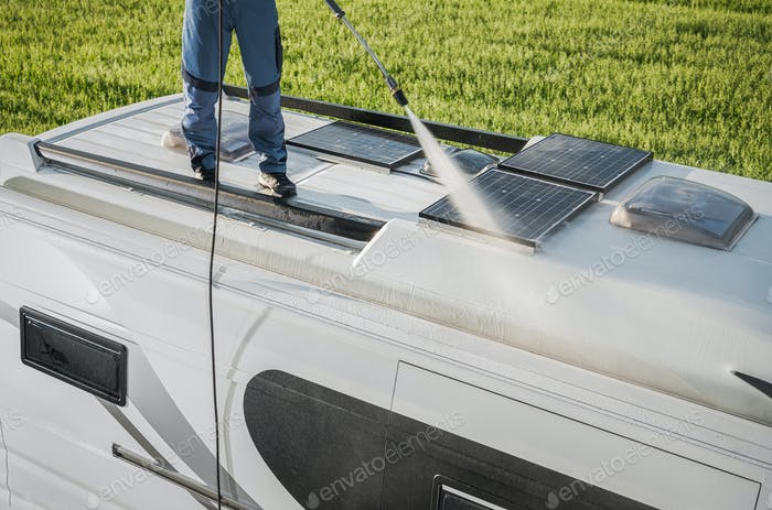 RV Industry Worker Cleaning Camper Van Roof and Motorhome Solar Panels