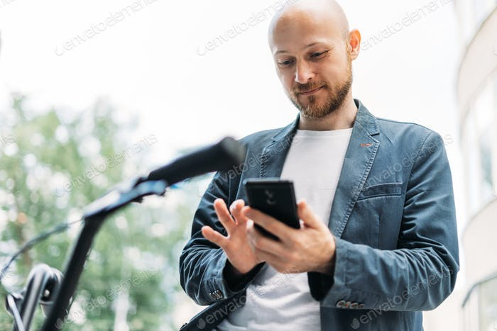 Adult bald bearded man in blue suit with mobile on bicycle