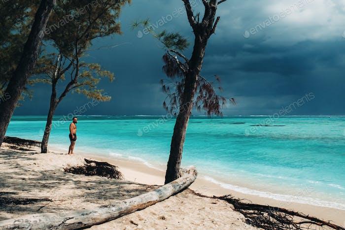 Apuesto joven relajado en pantalones cortos negros de pie en la playa