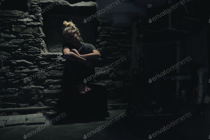 depressed anxious woman sitting in a dark corner of a basement