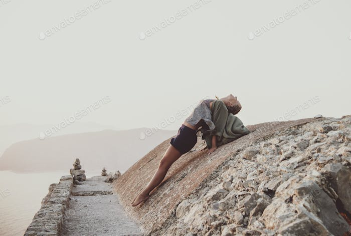 Woman stretching body on stones in Monolithos, Rhodes, Greece