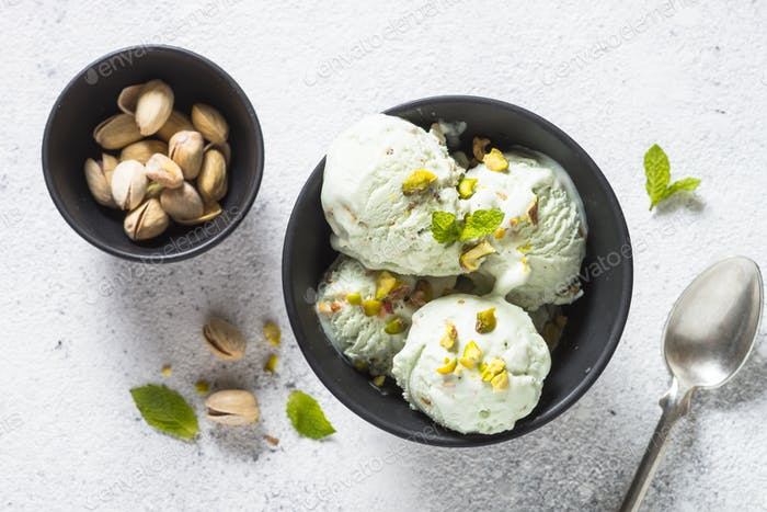 Pistachios ice cream in bowl on white stone table.