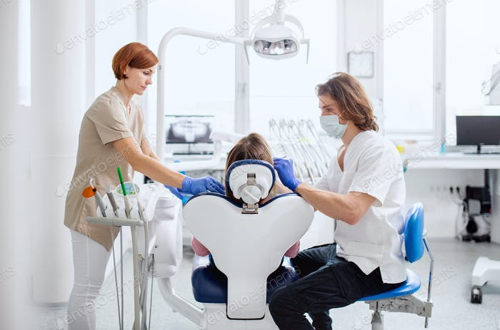 Man dentist and dental assistant at work in surgery, annual check-up