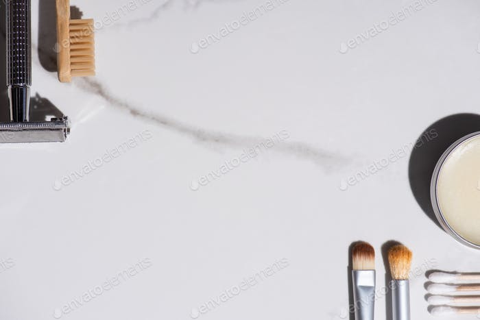 Top view of cosmetic brushes, toothbrush, razor, jar of wax