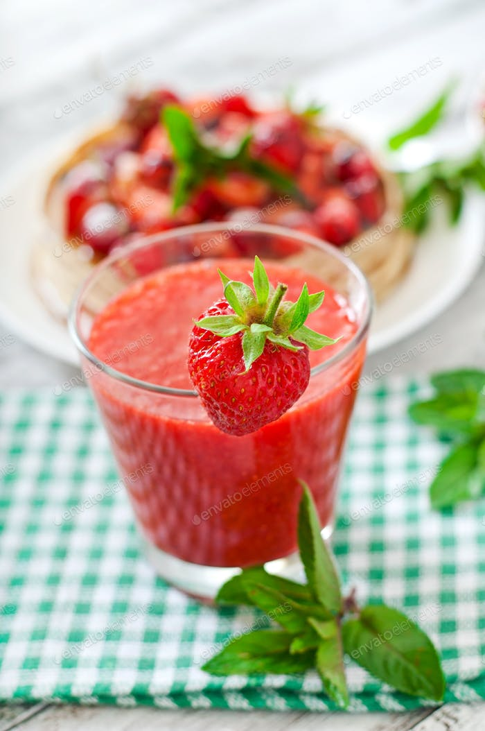 Strawberry smoothie in glass and mint leaves on a wooden background in rustic style