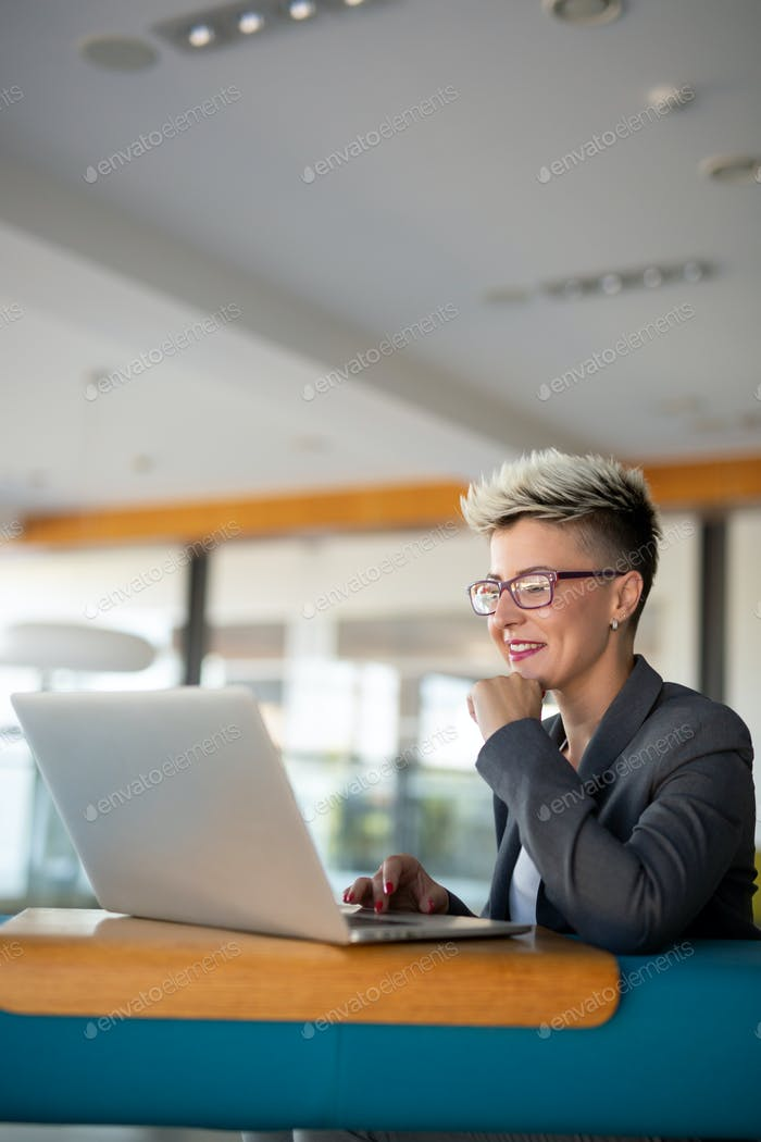 Young charming female freelancer using laptop computer for distance job while sitting