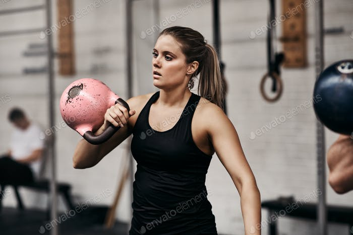 Fit young woman lifting a dumbbell at the gym