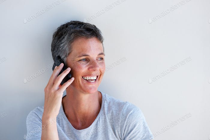 Close up beautiful middle age woman smiling and talking on mobile phone against white wall
