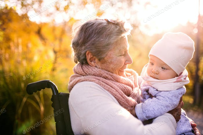 An elderly woman in wheelchair with baby in autumn nature.