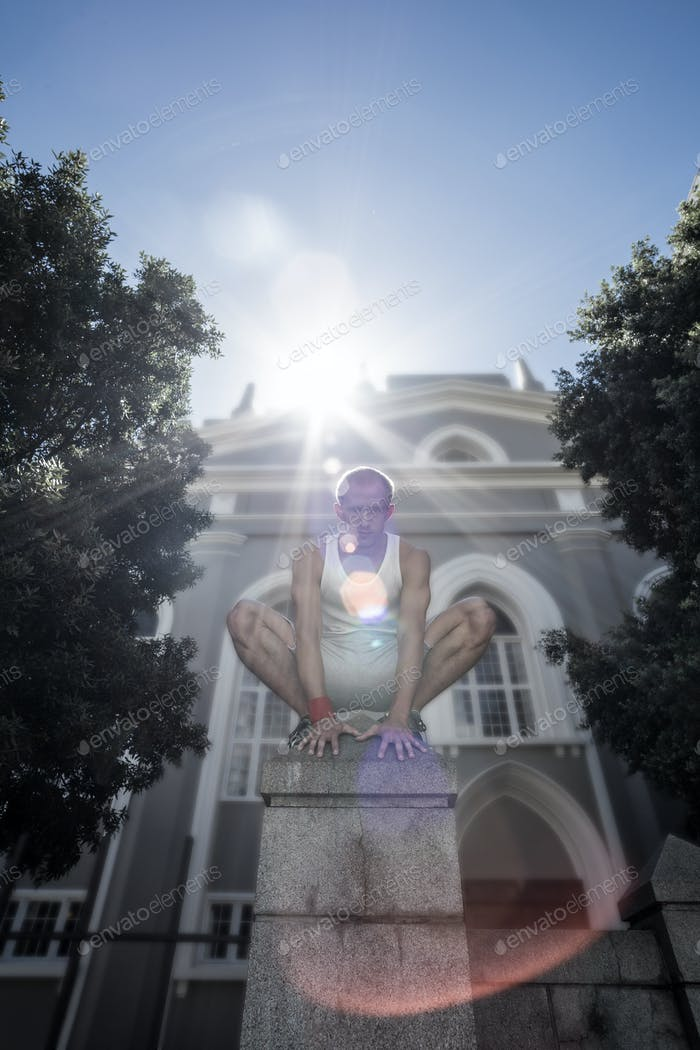Extreme athlete crouching on pillar in the city