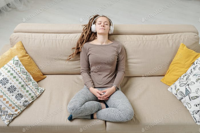 Restful woman in activewear sitting on couch and listening to peaceful music