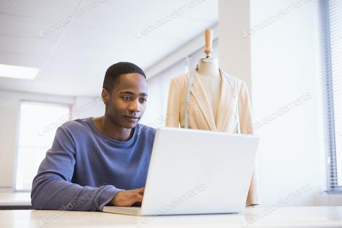 Smiling university student using laptop at the university