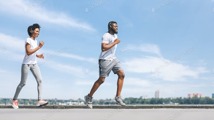 Cheerful African American Spouses Jogging Along River Embankment In Morning
