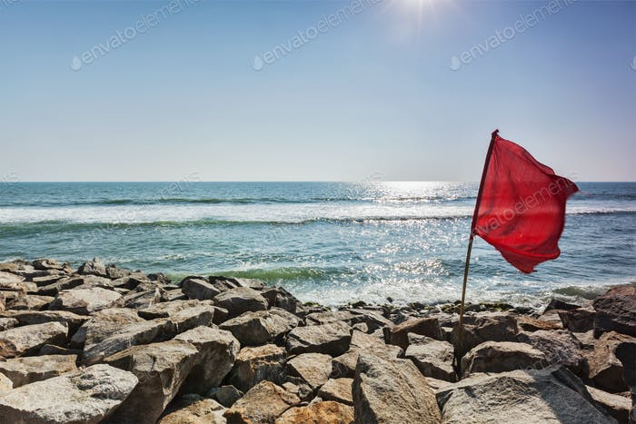 Red flag on rocky beach