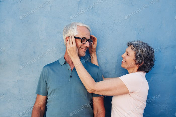 Woman adjusting the eyeglasses on her husband