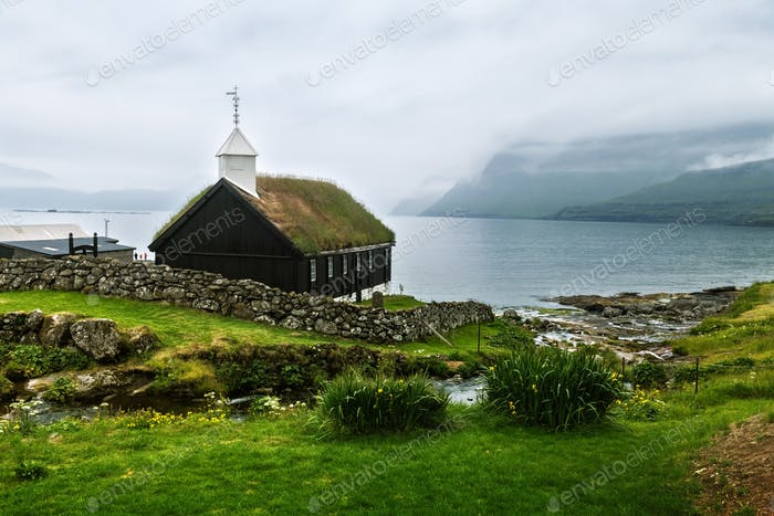 Summer view of traditional turf-top church in faroese village